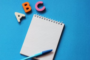 ABC-the first letters of the English alphabet on a blue background. Notebook and pen. Empty space for text. Learn foreign languages.