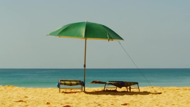 Hot day on the ocean, in the frame of a green umbrella and sunbed