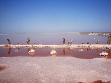 Extraction of salt in the estuary with red water. Salt pillars.