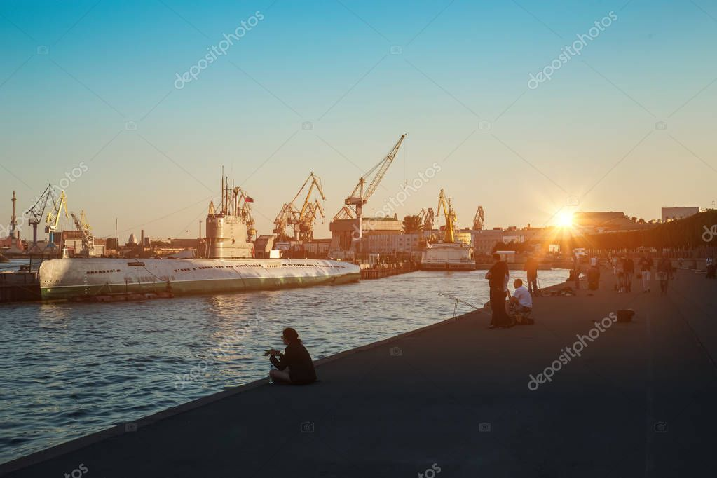 Beautiful evening sunset, visible port cranes and ships in the port on the Neva river, St. Petersburg, Russia. Vasilievsky island.