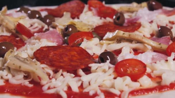 Masové pizzy. Na pizzu nalijte kapery. Vaření pizzy. Recept na pizzu s Salami. Potravní video. Video pro restaurace nebo kavárny. Pizza se vaří v italské restauraci. Makro střílení pizzy.
