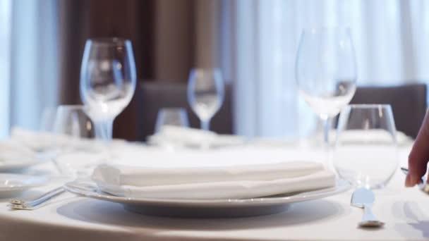 Číšník servíruje stůl v restauraci. Někdo nastavuje stůl v italské restauraci. Brýle na stole. jídlo video zblízka