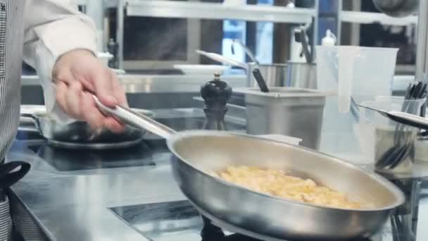 Tészta főzés a serpenyőben. Valaki főzés tészta. Élelmiszer-videó makró. Tészta előkészítés. Olasz konyha.