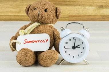 Teddy bear with a alarm clock and a label with the German word for summertime