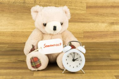 Teddy bear with a alarm clock and a label with the German word for daylight saving time