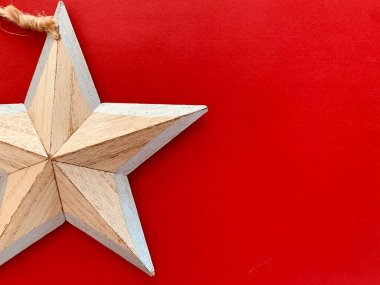 Background with wooden Christmas decorations star on red background. Space for text.