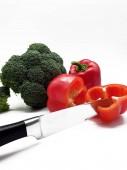 Červené papriky a brokolice na bílém pozadí