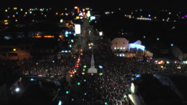 Aerial footage slow tilting down view of people crowd with beautiful light around Yogyakarta monument intersection, its called TUGU JOGJA