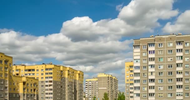 Time lapse clip of white fluffy rolling clouds against the background of yellow multi-storey apartment buildings