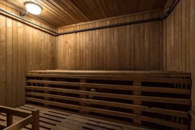 Large standard design classic wooden russian bath sauna interior with hot stones