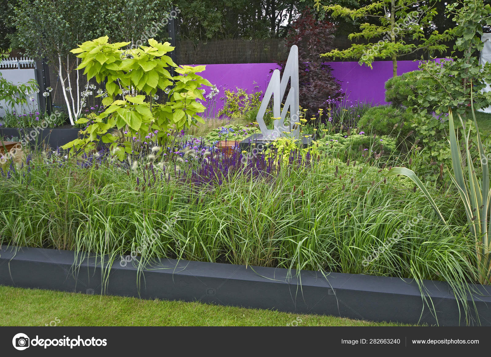 A Modern Garden With A Raised Grass Border To Mixed Planting Of