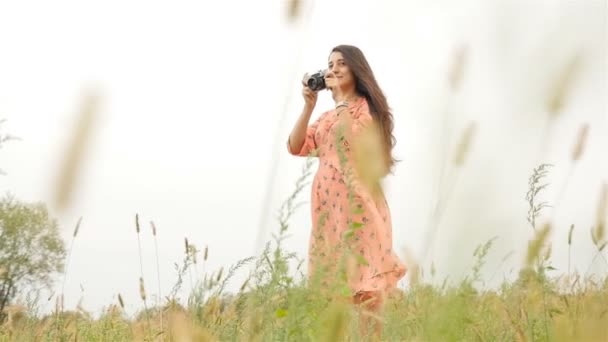 Beautiful girl with a camera photographs the landscape. Slow motion.