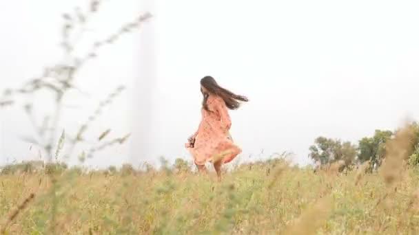 Beautiful girl whirls. Field with green grass. Long hair. Slender brunette. Slow motion