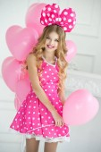Fotografie Funny girl with a bow. Happy birthday with pink balloons