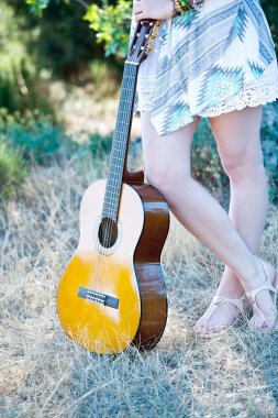 young woman posing with guitar at field