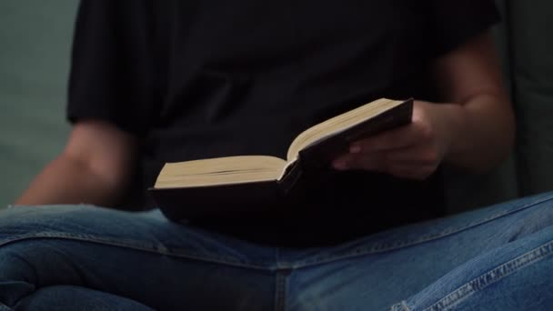 young woman in black t-shirt and blue jeans opens book