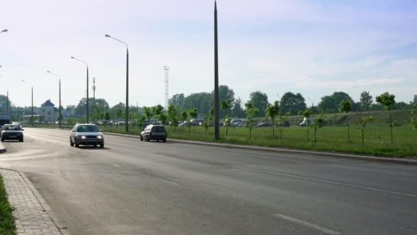 auta autem po šedé asfaltové silnici u mladých zahradních stromů