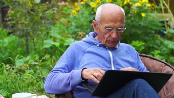 Ernsthafter Senior mit Brille arbeitet im Hinterhof an Notizbuch