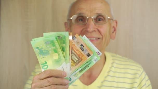 Lächelnder reicher Rentner schüttelt Hand mit Euro-Scheinen