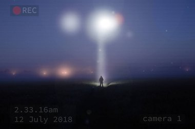 A security camera image of a silhouetted figure standing in a misty field at night watching a UFO in the sky, with a beam of light coming down.