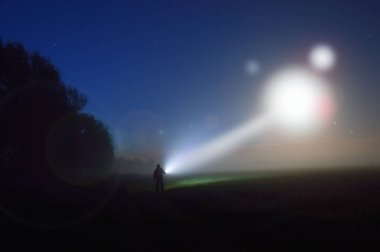 image of a silhouetted figure standing in a misty field at night watching a UFO in the sky, with a beam of light coming down.