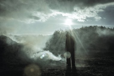 A lone hooded silhouetted figure standing outside. In a burnt smoking landscape. With a high contrast edit. With deliberate lens flare.