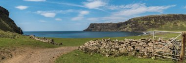 Talisker Bay, Isle of Skye, Scotland - Sandy beach with seaweed in the foreground and white surf and sea cliffs in the distance. panorama.