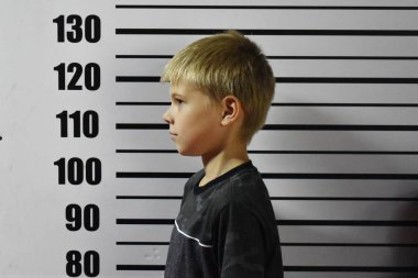 a convicted teenager is standing against a wall in the police.