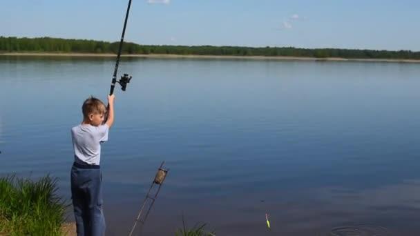 Sohn angelt am Ufer eines Teiches zum Spinnen. Angeln Hobbys für Kinder...