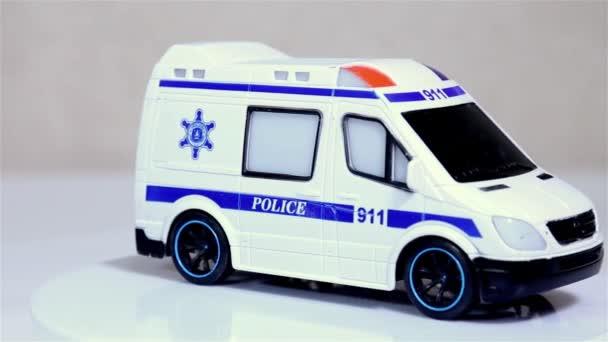 Bílá policejní autobus měřítko modelu autíčko otáčí na bílém pozadí.