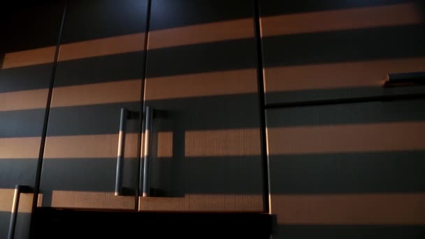 Striped shadows from moving Venetian blinds are displayed on kitchen cabinets. Animated background texture.
