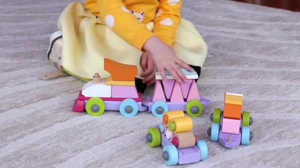 Little girl plays with educational toy train, sitting on a floor at home .