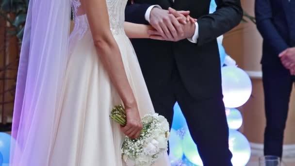Nevěsta a ženich drží ruce na svatební slavnosti. Žena v bílých šatech držící kytici růží.