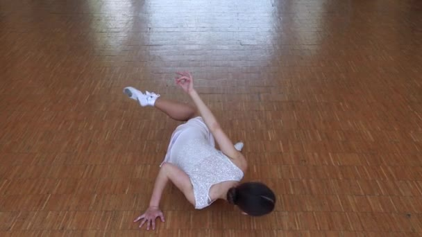 Young thin ballerina in white dress dancing on a floor in studio..