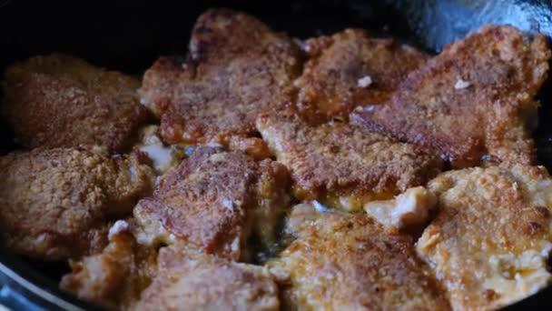 Kousky šťavnatého vepřového masa smaženého v oleji na pánvi zblízka.