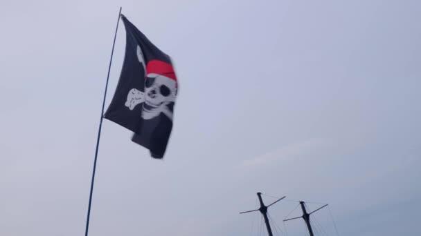 Bandiera pirata Jolly Roger appeso su un albero nave su uno sfondo cielo blu al giorno ventoso.