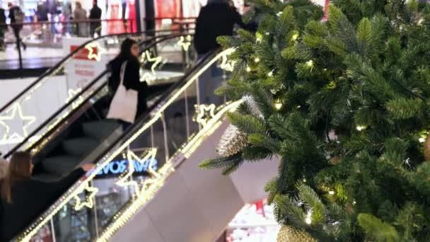 Vánoční výzdoba v nákupním centru. Lidé na eskalátoru, nakupujte,.