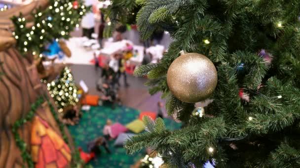 Zlatý míč a věnce na umělém vánočním stromečku v zdobeném nákupním centru.