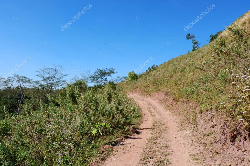 dirt road side / dirt road field on hill to mountain - Rural dusty countryside road trough for off road truck