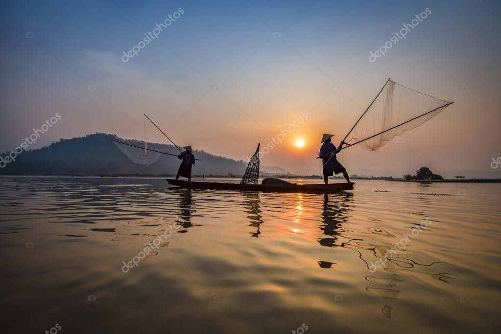 Fisherman on boat river sunset / Asia fisherman net using on wooden boat casting net sunset or sunrise in the Mekong river - Silhouette fisherman boat with mountain background life person countryside