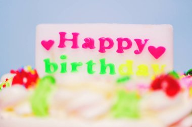 Colorful birthday cake with label of  happy birthday and heart shaped Close up
