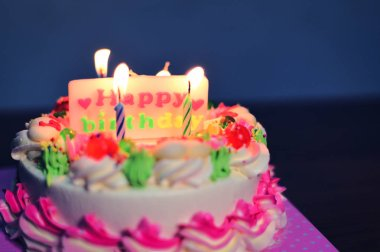 Colorful birthday cake with candles lights on the table at night with label of  happy birthday