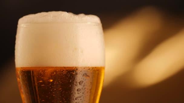 Részlet lövés forgó sötét háttér és üveg csepp friss sör