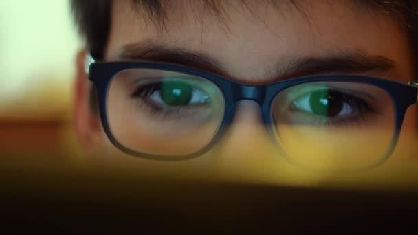 Mladý chlapec, který nosí brýle sleduje obrazovku počítače