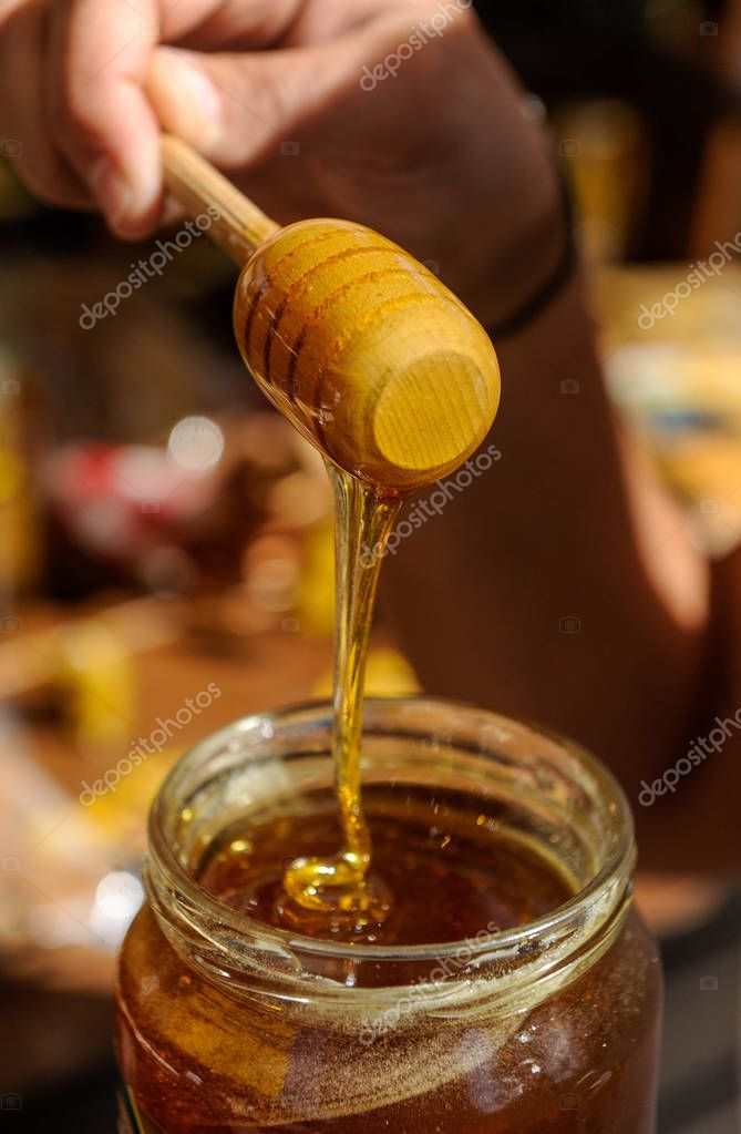Honey dripping from honey dipper in the glass jar
