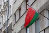 Národní vlajka a erb Běloruské republiky na budově.