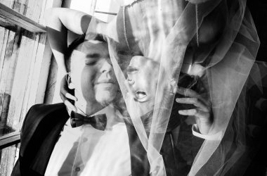 stylish bride and groom at a wedding photo session in the studio, a couple in love is lying on the floor near the window, the photo is in a hard light
