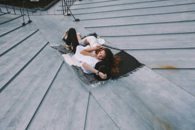 couple in love lying on the roof of the house and hugging - a girl in a white dress and a guy with a hat - view from the roof of the city, positive and sincere emotions of love