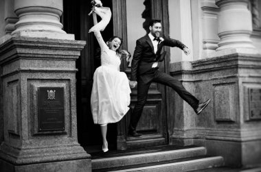 excited bride and groom jumping after registration, black and white photo