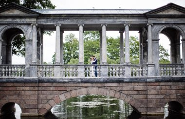 stylish bride and groom on their wedding day embracing and smiling while walking in a summer park on a stone bridge